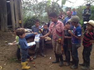 Isaac passing literature to childrens in the Chimizal village